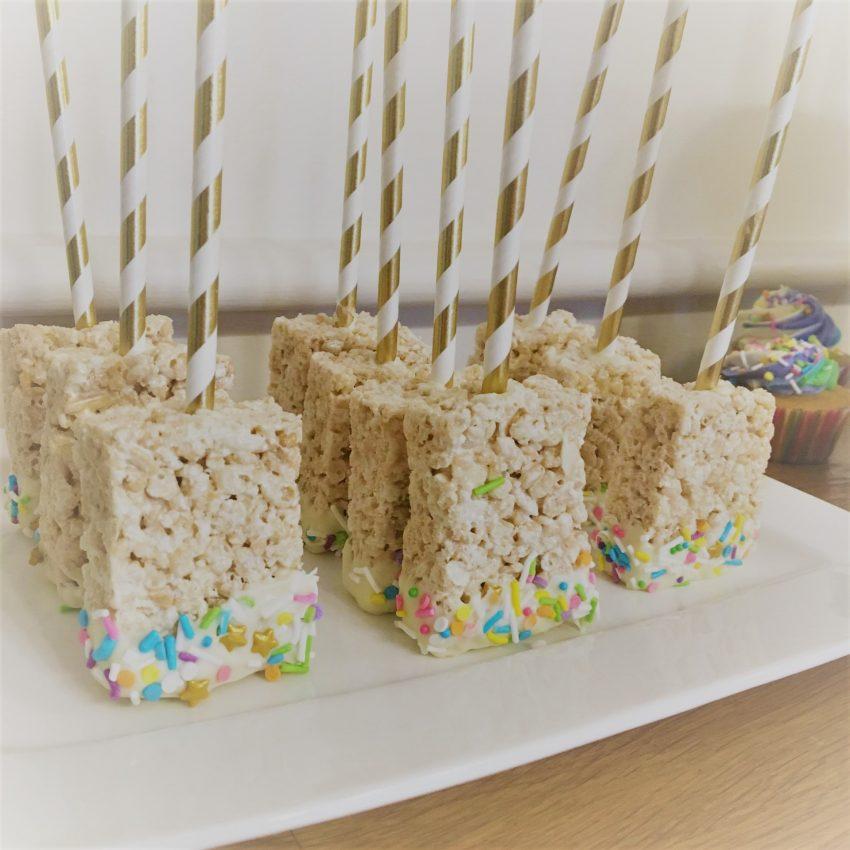 Les fameux carrés de riz soufflé... On plante une série de bâtons dans le mélange avant de le mettre au frigo, puis on fait trempette dans le chocolat fondu et les bonbons multicolores!